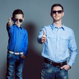 Two gentlemen: young father and his little cute son in sunglasse. S. Are dressed in blue shirts and jeans. They are happy. Studio shot Royalty Free Stock Photography