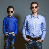 Two gentlemen: young father and his little cute son in sunglasse. S. Are dressed in shirts and jeans. Studio shot Stock Photo