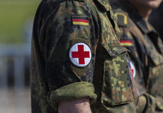 Two german army soldiers with a red cross brassard. BERLIN / GERMANY - JUNE 3, 2016: two german army soldiers with a red cross brassard Royalty Free Stock Photo