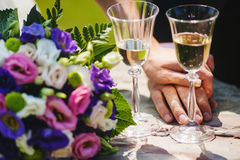 Two Gglasses with Champagne, Couple Hands, Bouquet Royalty Free Stock Image
