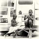 Two Ghanaian children sit on the bench near the ro Stock Images