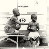 Two Ghanaian children sit on the bench near the ro Royalty Free Stock Photos