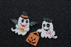 Two ghosts carrying an orange trick or treat bag on a black background stock photography