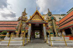 Two giant stand  in front of the gate in the Wat Phra Kaew, Bangkok, Thailand. This picture was taken in Wat Phra Kaew, Bangkok, Thailand Royalty Free Stock Images