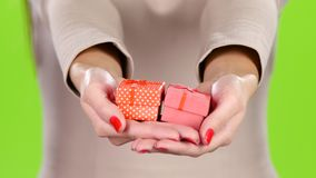Two gift box in the hands of women. Close up. Two gift box in the hands of women, give gift boxes, small cardboard box wrapped in pink and polka dot wrapping stock footage