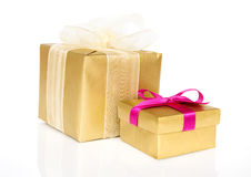 Two gift boxes. Two golden gift boxes isolated over white background with reflection Stock Image