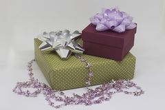 Two gift boxes and beads on a light background. Two gift boxes - green and burgundy with a bow and beads on a light background Stock Photos