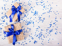 Two gift boxes with blue ribbons on a white background with sparkles. Copy space. Two gift boxes with blue ribbons on a white background with sparkles stock photography