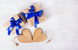 Two gift boxes with blue ribbons and wooden hearts on a white background. Valentine`s Day. Copy space. Stock Photography