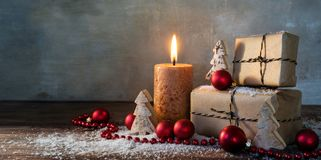 Two gift boxes and a burning candle, red christmas baubles and s. Two gift boxes and a burning candle decorated with red christmas baubles and small wooden toy Royalty Free Stock Image