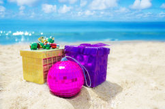Two gift boxes with Christmas ball on the beach - holiday concep Royalty Free Stock Photo