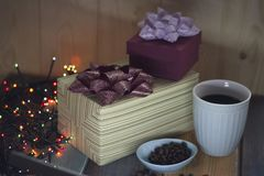 Two gift boxes, coffee beans in a bowl, a cup of coffee on a tablennn Royalty Free Stock Image
