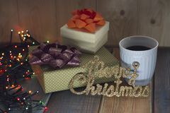 Two gift boxes, cup of coffee and Marry Christmas on the tablenn Royalty Free Stock Photo