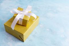 Two gift boxes in gold paper witn white bow on blue background. Holiday concept. New year, christmas, birthday Stock Images