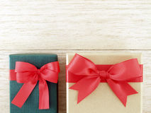 two gift boxes (green and golden) with red ribbon bow on wooden table floor Stock Photos