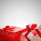 Two gift boxes with hearts printed with grey background closeup Royalty Free Stock Photo