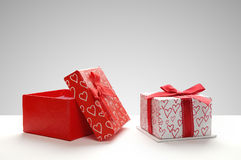 Two gift boxes with hearts printed with grey background front Royalty Free Stock Photography