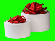 Two gift boxes. The image of two white gift round boxes with red tapes is on a green background Stock Photography