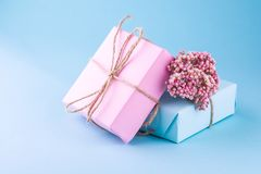 Two gift boxes of pink and blue with bows of twine decorated with small pink flowers on a blue background. stock image