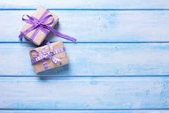Two gift boxes with presents on blue wooden background. Royalty Free Stock Photo