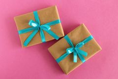 Two gift boxes wrapped of craft paper and blue ribbon on the pink background. Royalty Free Stock Photos