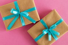 Two gift boxes wrapped of craft paper and blue ribbon on the pink background. Stock Image
