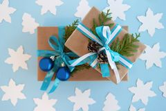 Gift boxes wrapped of craft paper, blue and white ribbon and decorated fir branches, blue Christmas balls and pinecones. Stock Image