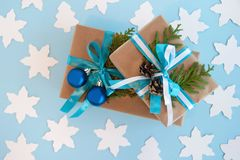 Two gift boxes wrapped of craft paper, blue and white ribbon and decorated fir branches, blue Christmas balls and pinecones. Stock Images
