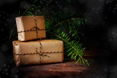 Two gift boxes wrapped in kraft paper under a fir branch for chr. Istmas, some bokeh lights, dark background with copy space, selected focus Royalty Free Stock Image