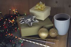 Two gifts, a cup of coffee Christmas balls and sweet sticks n Stock Images