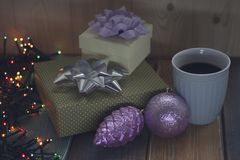 Two gifts, cup of coffee, cone, ball, the lights on the tablenn Royalty Free Stock Photography
