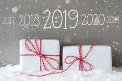 Two Gifts With Snowflakes, Text 2019, Snowy Cement Background. Text 2019 For Happy New Year. Two White Christmas Gifts Or Presents On Snow. Cement Wall As stock photos