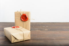 Two gifts wrapped in craft paper with rope and red sealing wax o. Ver brown wooden table and white background stock photos