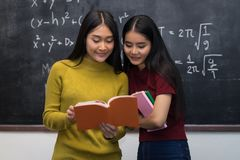 Two gilrs are cheerful beautiful reading a book on the board bac Stock Photography