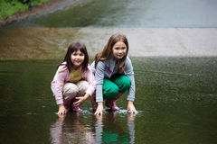Two gilrs squatting in a stream. Two young girls squatting in the middle of a stream Stock Photo