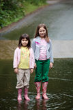 Two gilrs standing in a stream. Two young girls standing in the middle of a stream Stock Photography