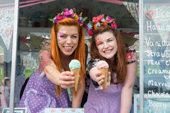 Two ginger haired ladies holding ice cream from truck. Two ginger haired ladies smiling wearing vintage spotted dresses holding ice cream out of truck stock photo