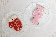 Two gingerbread cookies in the shape of candy and red mitten on a white napkin background. Top view, flat lay, copy. Space. Curly Christmas gingerbread home Royalty Free Stock Images