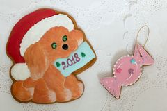 Two gingerbread cookies in the shape of Christmas dog and candy on a white napkin background. Top view, flat lay, copy. Space. Curly Christmas gingerbread home Stock Image