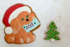 Two gingerbread cookies in the shape of Christmas tree and dog on a white napkin background. Top view, flat lay, copy. Space. Curly Christmas gingerbread home Royalty Free Stock Images