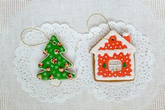 Two gingerbread cookies in the shape of the Christmas tree and small house on a white napkin background. Top view, flat. Lay, copy space Stock Image