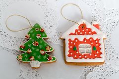 Two gingerbread cookies in the shape of the Christmas tree and small house on a white napkin background. Top view, flat. Lay, copy space Royalty Free Stock Images