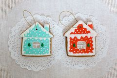 Two gingerbread cookies in the shape of the small cottage on a white napkin background. Top view, flat lay, copy space. Curly Christmas gingerbread home Royalty Free Stock Photo