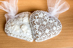 Two gingerbread heart cookies on wooden table Stock Photo