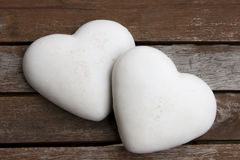 Two gingerbread hearts. Covered by white icing, on the wooden surface Royalty Free Stock Image