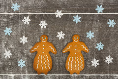 Two gingerbread ladies together on floury table. Stock Photo