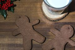 Two gingerbread man cookies with a glass of milk on a wooden backgroun, close up stock image