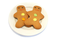 Two Gingerbread men on a Plate. Two Gingerbread men on a cream plate on a white background Royalty Free Stock Photo
