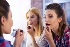 Two girl applying lipstick Royalty Free Stock Image