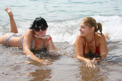 Two girl on a beach. The blonde and the brunette in the sea stock images